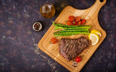 Juicy steak rare beef with spices on a wooden board and garnish of asparagus. Flat lay. Top view